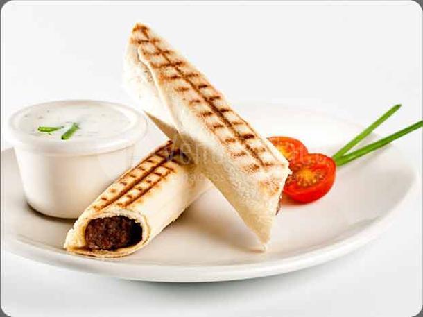 Rollito de pan de pita relleno de carne, acompañado con una deliciosa salsa de yogur con pepino del Restaurante Shukran