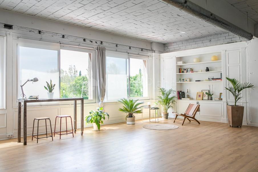 Zona ventanales con biblioteca open space en Take loft BCN